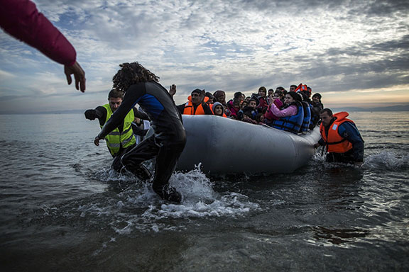 Refugees and migrants are helped by volunteers on their arrival aboard a dinghy at Mytilene on the northeastern Greek island of Lesbos, Tuesday, Feb. 23, 2016. Nearly 100,000 migrants and refugees have traveled to Greek islands from nearby Turkey so far this year. (AP Photo/Manu Brabo)
